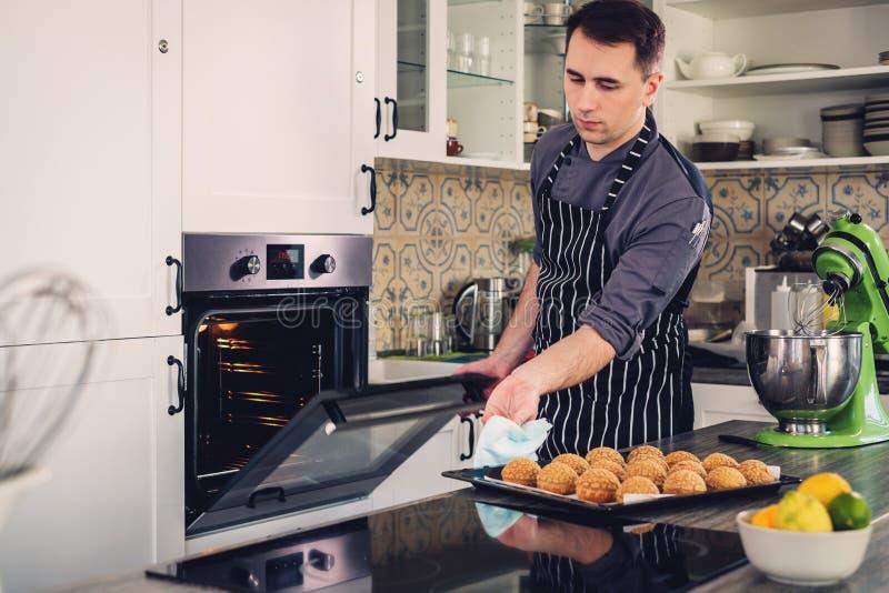 Kockkock som hemma arbetar på ett modernt kök arkivbild
