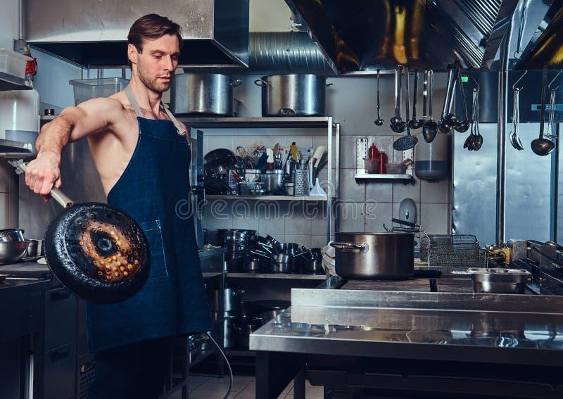 Kockkocken rymmer den varma stekpannan arkivfoton