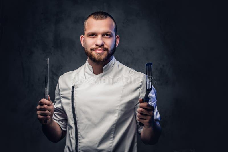 Kockkocken rymmer en kniv över mörk grå bakgrund royaltyfria foton