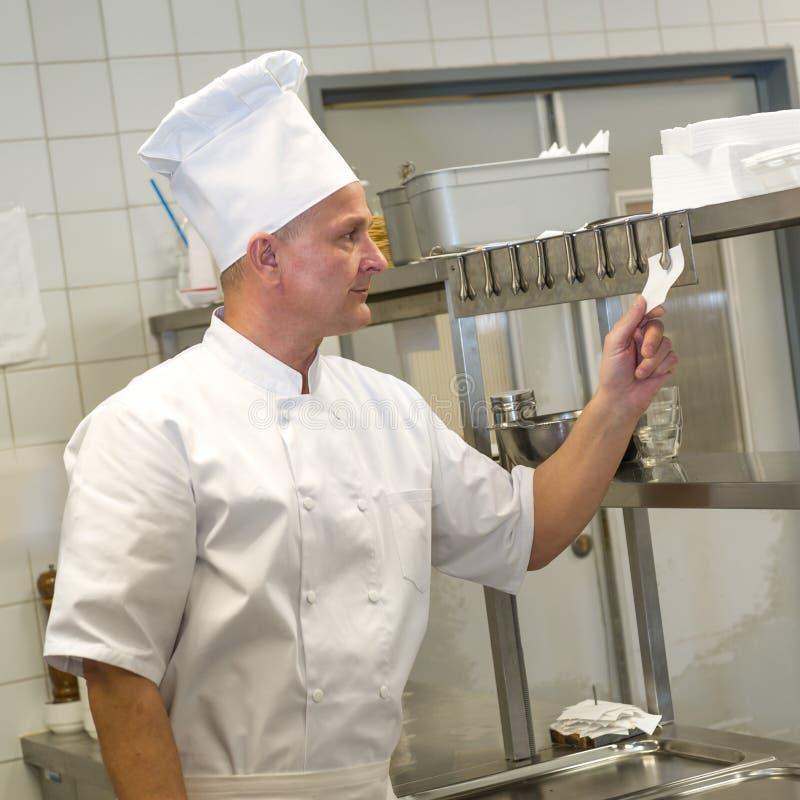 Kockläsningbeställningar i restaurangs kök royaltyfria bilder