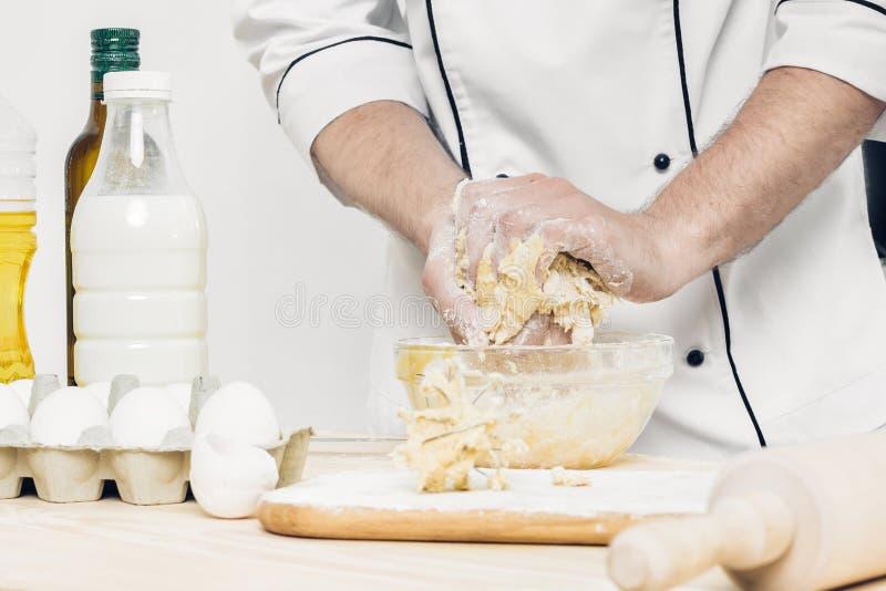 Kockman i likformig som knådar rå deg i kök arkivfoto
