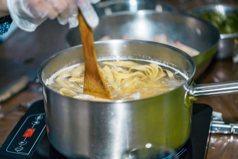 Kockuppståndelsespagetti i en kruka av kokande vatten Matlagningspagetti arkivbild