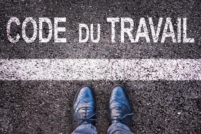 Kod för arbete för koddu slavgöra betydelse i franskt skriftligt på en bakgrund för asfaltväg med ben royaltyfria foton
