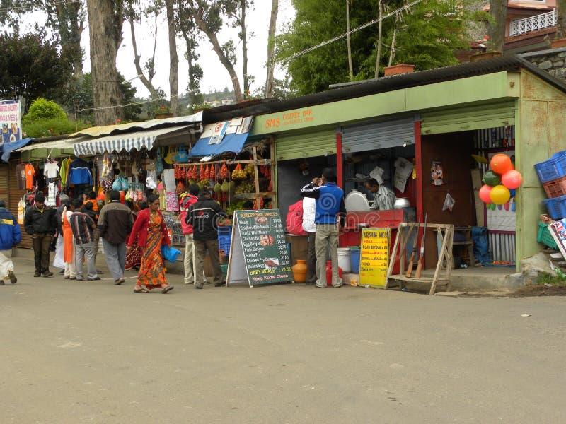 Kodaikanal, Tamil Nadu, Indien - 11. Juni 2010 kauft bunte Straßenseite, klemmt, Lebensmittel, Tee, Snäcke verkaufend nahe Kodaik lizenzfreies stockbild