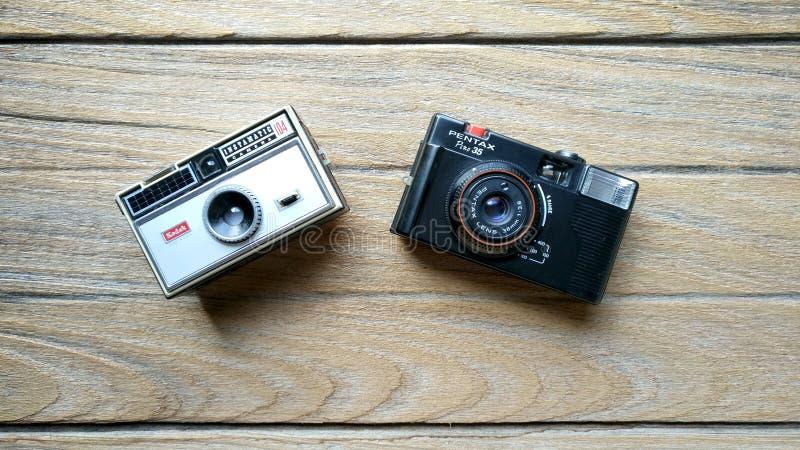 Kodak instamatic 104 and Pentax Pino 35. BANGKOK, THAILAND - MARCH 20, 2017 : Kodak instamatic 104 camera and Pentax Pino 35 on a wood table stock photos