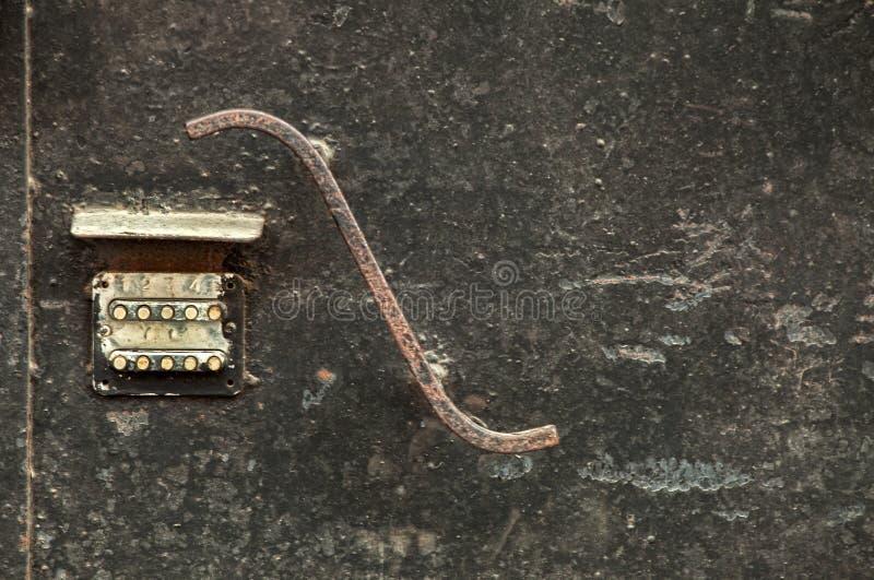 Kodat lås på gammal rostig skalningsmetalldörr med det lockiga handtaget royaltyfria bilder