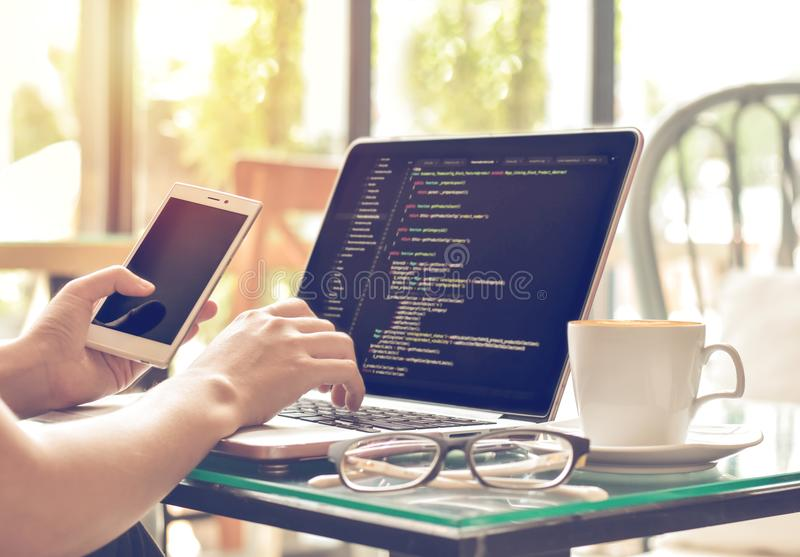 Koder för en källa för kvinnligprogrammeraremaskinskrivning och användamobiltelefon i en coffee shop royaltyfri fotografi