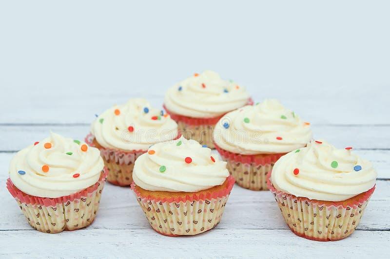 Koekje cupcakes met room in document vormen Op witte houten achtergrond royalty-vrije stock afbeeldingen