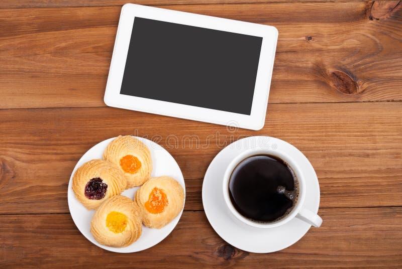 Koekjes en digitale de tabletcomputer van de koffiekop stock afbeelding