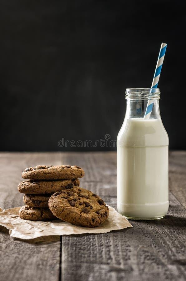 Koekjes en een fles melk stock foto