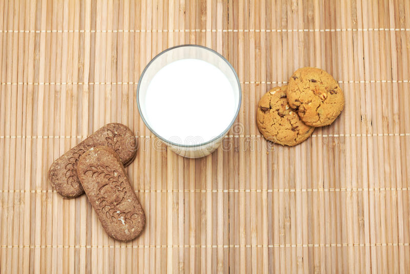 Koekjes en een glas melk op een doek van de bamboelijst stock afbeeldingen
