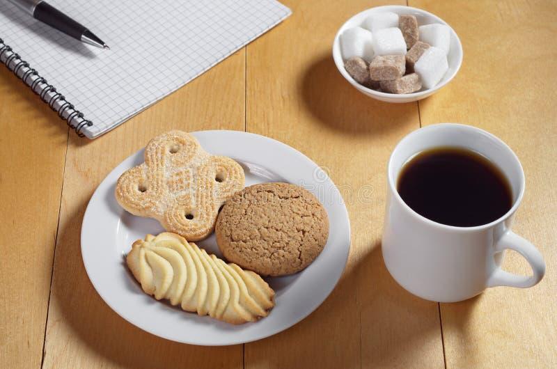 Koekjes, koffie en notitieboekje stock afbeeldingen