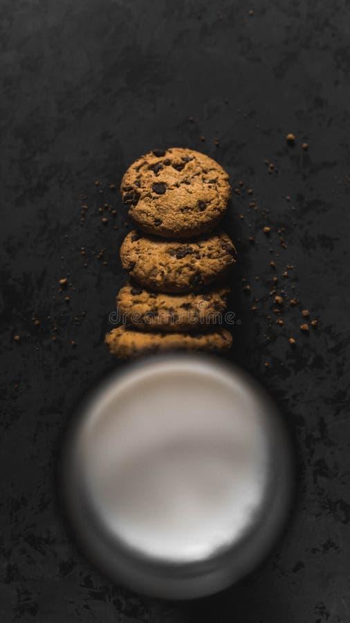 Koekjes met chocoladeschepen en melk met een donkere achtergrond royalty-vrije stock foto