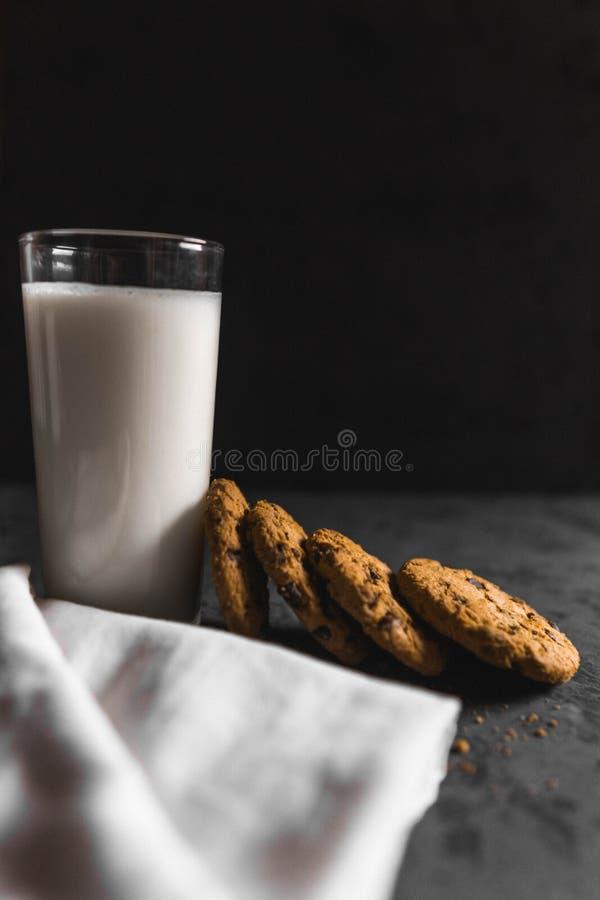 Koekjes met chocoladeschepen en melk met een donkere achtergrond royalty-vrije stock afbeelding