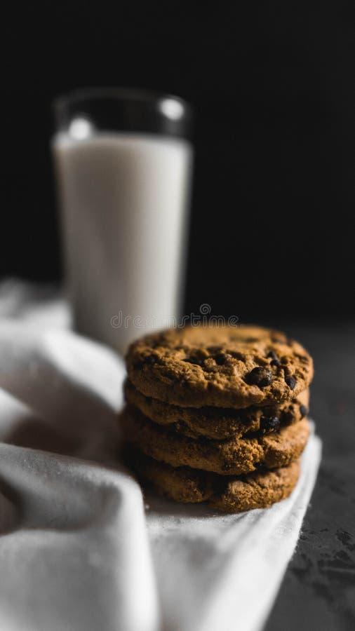 Koekjes met chocoladeschepen en melk met een donkere achtergrond stock foto