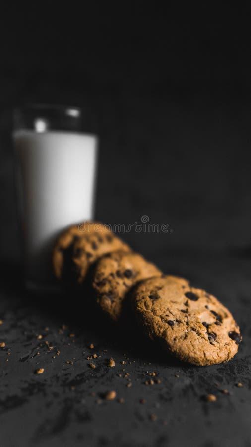 Koekjes met chocoladeschepen en melk met een donkere achtergrond stock afbeelding