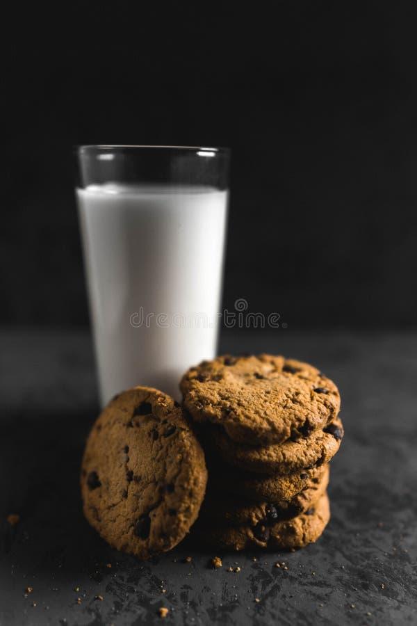 Koekjes met chocoladeschepen en melk met een donkere achtergrond royalty-vrije stock afbeeldingen