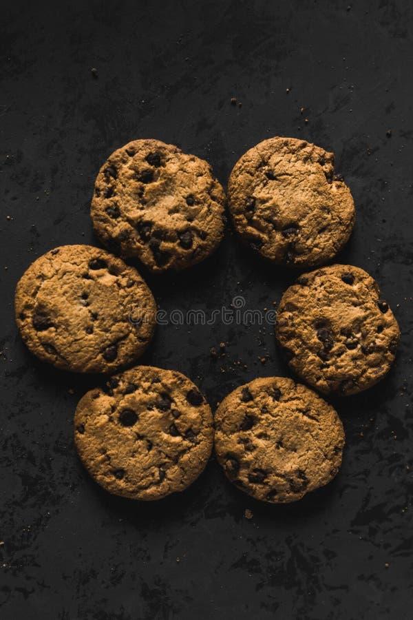 Koekjes met chocoladeschepen op een donkere achtergrond stock afbeelding