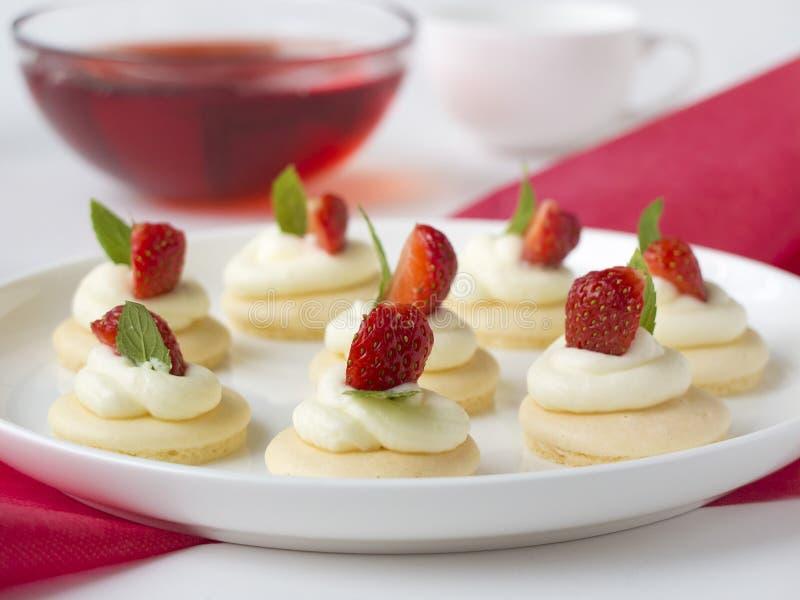 Koekjes met slagroom, strawsberry, munt op witte plaat op lijst tegen lichte achtergrond stock afbeelding