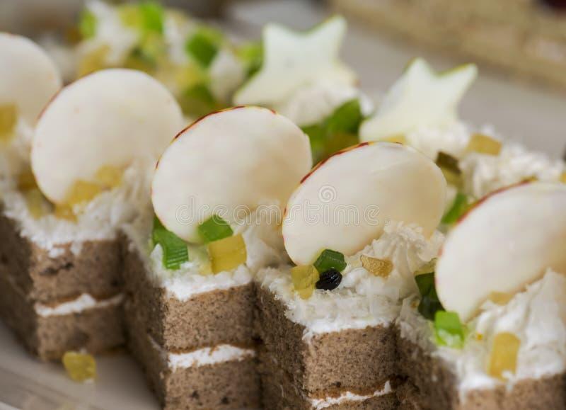 Koekjescake, met room wordt verfraaid, plakken van gelei en witte chocolade op een witte plaat die Selectieve nadruk stock foto