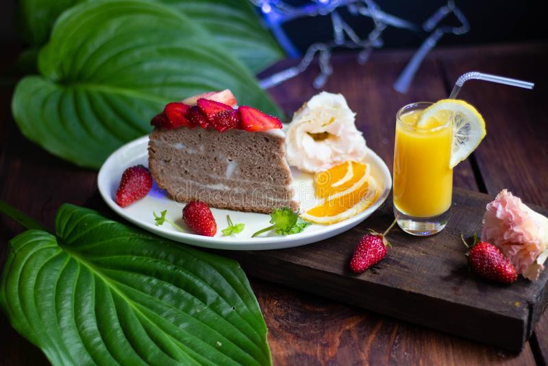 Koekjescake met zure room die met aardbeien, verse bes op een dienblad, met blauwe lichten op de achtergrond wordt verfraaid royalty-vrije stock foto