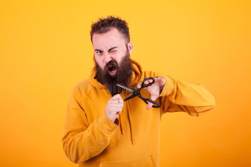 Koel de gebaarde mens die angst aangejaagd terwijl het snijden van zijn baard over gele achtergrond kijkt stock fotografie