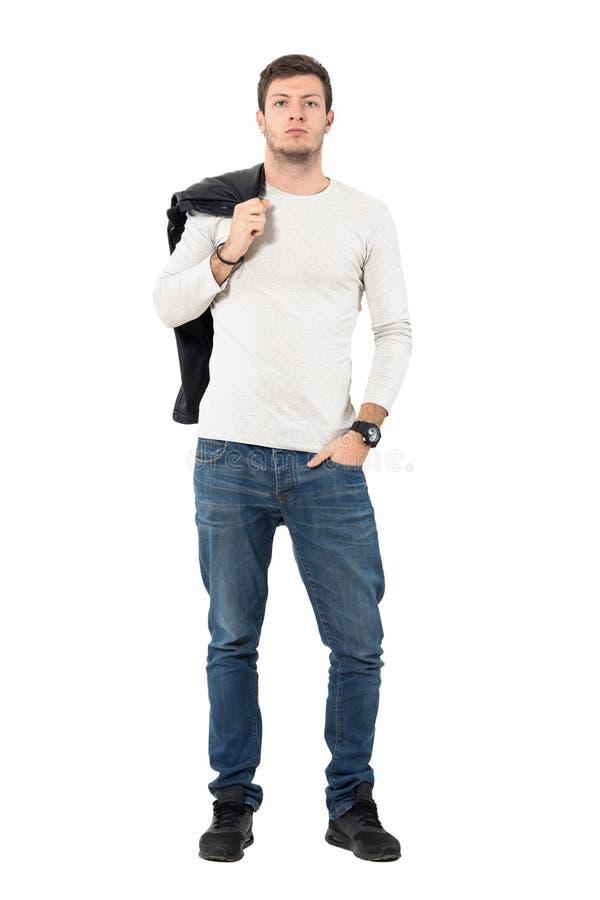 Koel de knappe mens in jeans die leerjasje over schouder dragen bekijkend camera stock fotografie