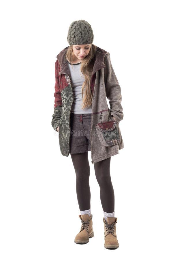 Koel de spontane jonge vrouw die van de hipsterstijl in warme de winterlaag en wollig GLB neer kijken stock afbeeldingen