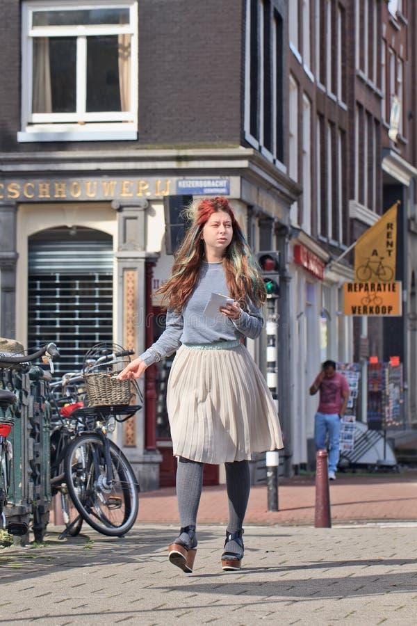 Koel het geklede meisje lopen op de straat, Amsterdam, Nederland stock foto's