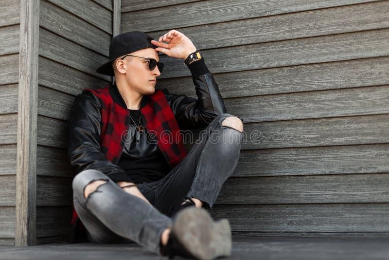 Koel hipster de jonge mens in in donkere zonnebril in een uitstekend rood en zwart geruit jasje met leerkokers in jeans stock afbeelding