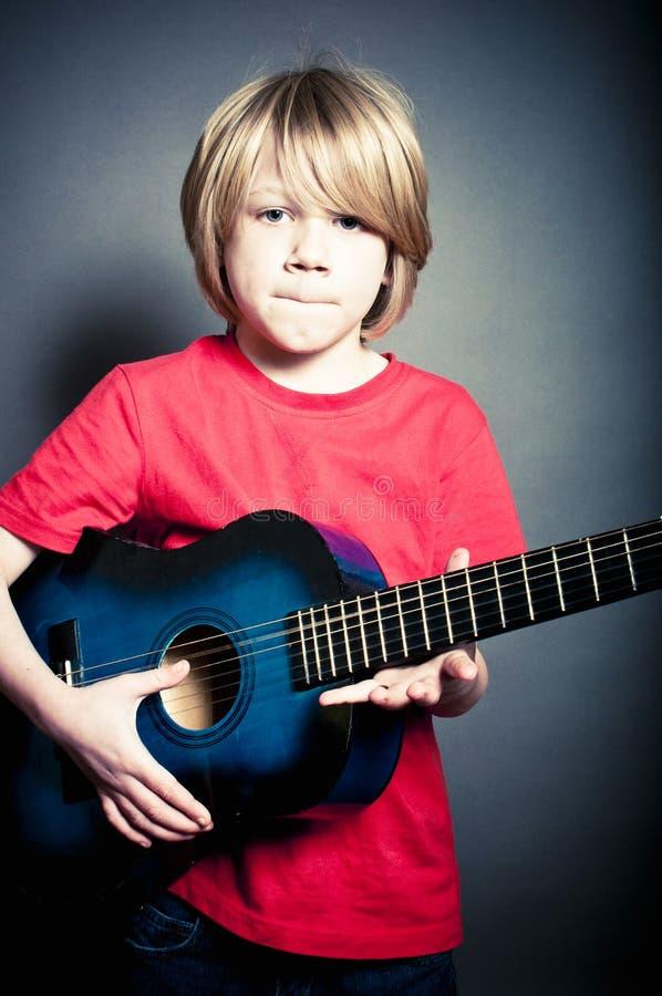 Koel jong mannelijk model met een accoustic gitaar stock foto's