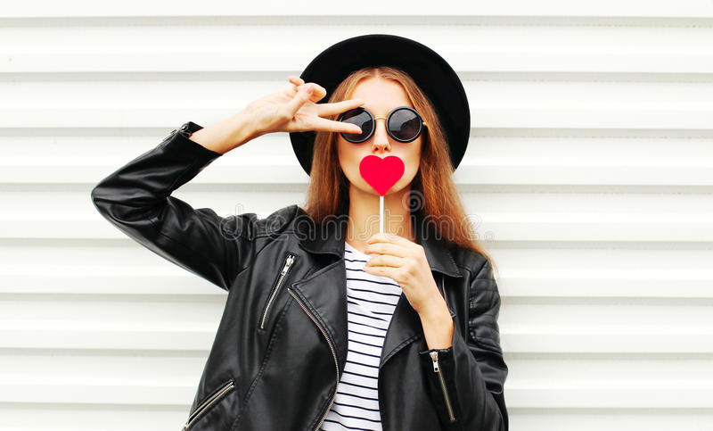 Koel jong meisje met rood lollyhart die het leerjasje van de manier zwart hoed over witte stedelijk dragen royalty-vrije stock foto's