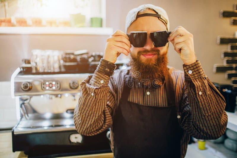 Koel jong Nd van de baristatribune stellen op camera Hij draagt zonnebril in keuken Kerelglimlachen Hij kijkt gelukkig stock afbeelding