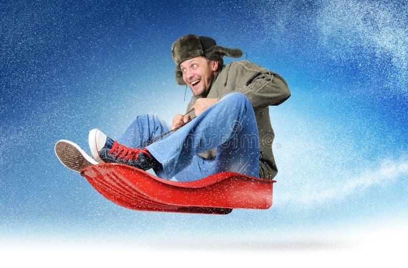 Koel jonge mensenvlieg op een slee in de sneeuw stock fotografie