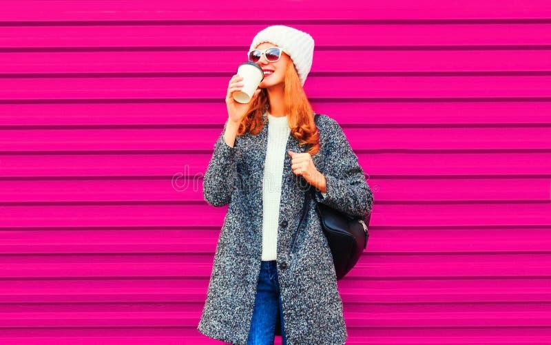 koel meisje die smakelijke koffie drinken die grijze laag, gebreide hoed o dragen royalty-vrije stock foto