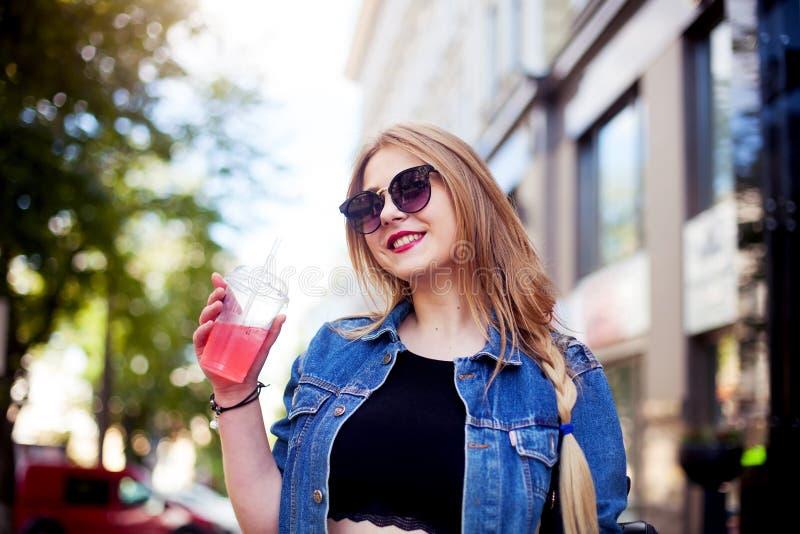 Koel meisje met lang kapsel en rode lippen die pret in de stad hebben Zij draagt zonnebril en het glimlachen aan camera royalty-vrije stock afbeeldingen