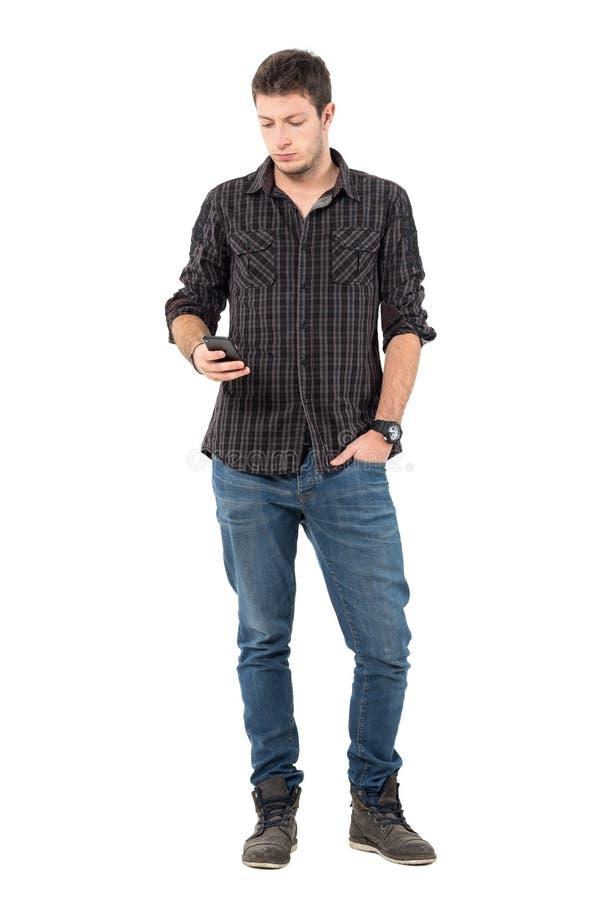 Koel ontspannen jong toevallig mens het typen bericht op mobiele telefoon stock foto's