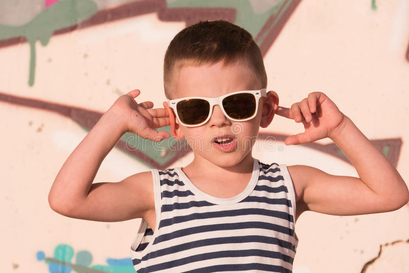 Koel weinig jongen die zonnebril en gestreept vest op graffitiachtergrond draagt royalty-vrije stock afbeelding