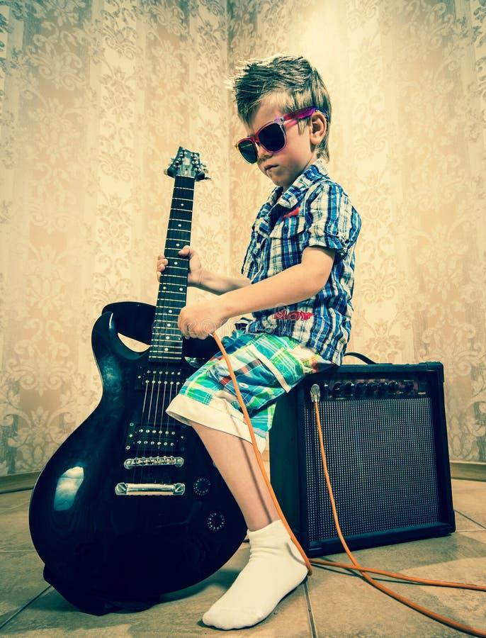 Koel weinig jongen het stellen met elektrische gitaar royalty-vrije stock foto