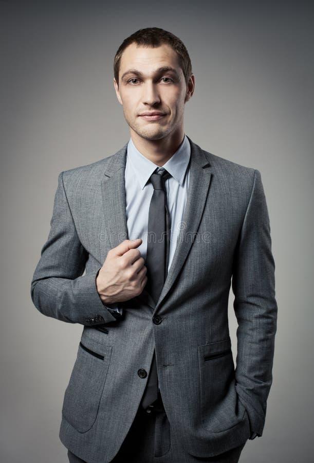 Koel zakenmanportret op grijs stock foto