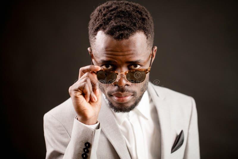 Koele Afrikaanse kerel die zonnebril dragen die door hen kijken royalty-vrije stock afbeelding