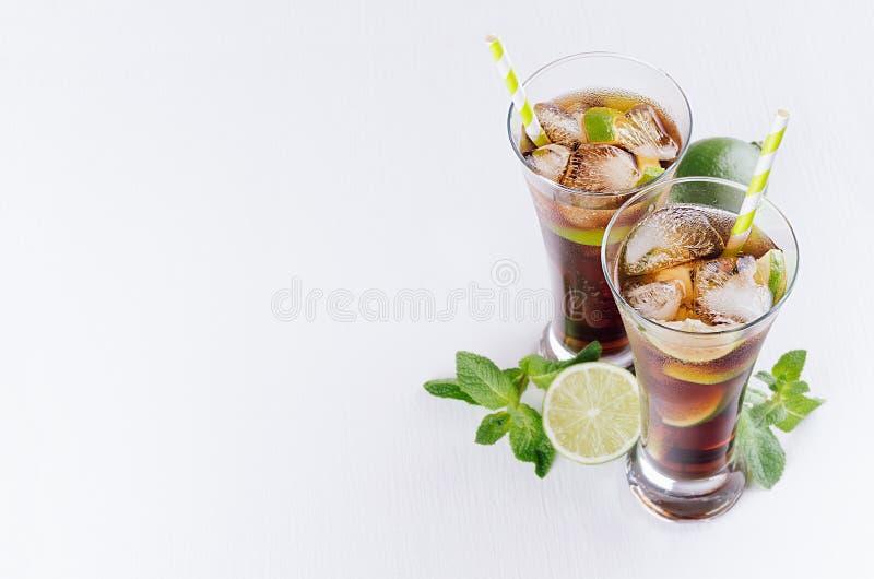 Koele cocktailrum en kola in glazen met bellen, ijsblokjes, kalk, bladmunt op zachte lichte witte achtergrond met exemplaarruimte royalty-vrije stock fotografie