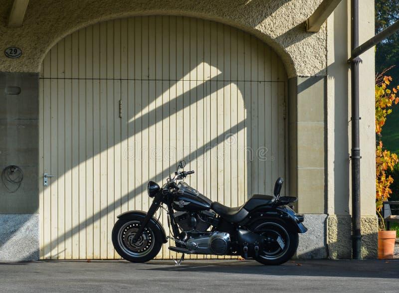 Koele die motorfiets dichtbij de garage wordt geparkeerd stock afbeeldingen