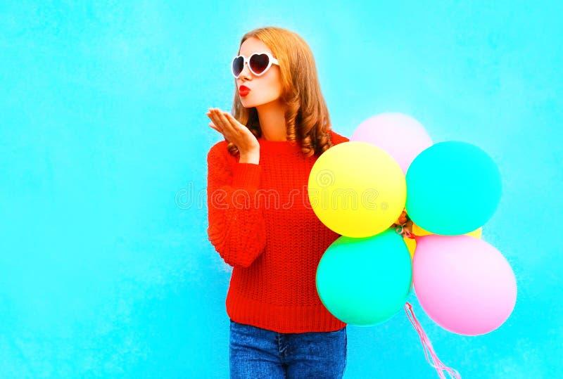 Koele gelukkige gir lsends een luchtkus met kleurrijke ballons op blauw stock foto