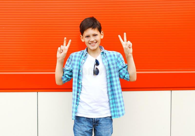 Koele glimlachende kindjongen die pret in stad over rood hebben stock fotografie