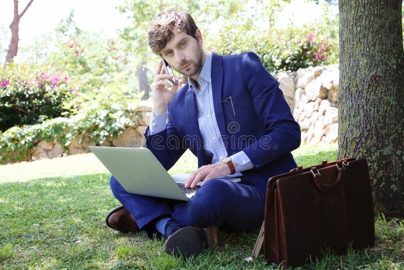 Koele het werk zakenmanzitting op het gras in een stadspark royalty-vrije stock afbeeldingen