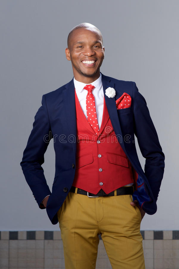 Koele jonge Afrikaanse mens die in modieus kostuum in openlucht glimlachen royalty-vrije stock fotografie