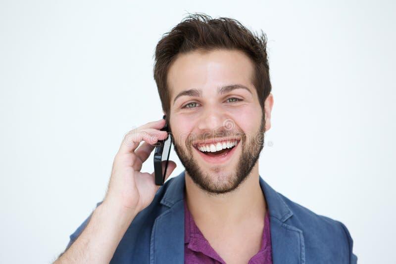 Koele jonge mens die met mobiele telefoon op witte achtergrond glimlachen royalty-vrije stock afbeelding