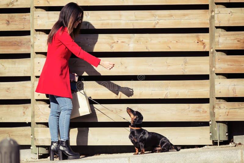 Koele jonge mooie vrouw die haar zoete hond playfuly in de straat voedt royalty-vrije stock fotografie
