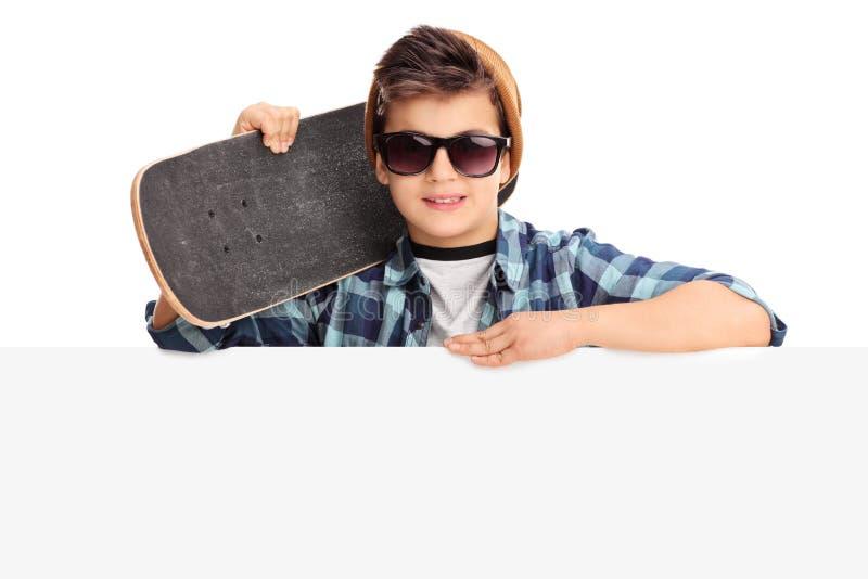 Koele jongen die een skateboard achter paneel houden stock foto's